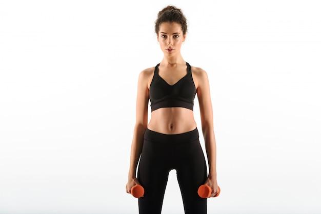 Calma fitness mulher em pé com halteres