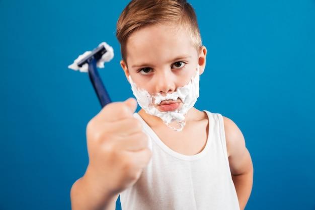 Calma jovem em espuma de barbear como homem mostrando navalha