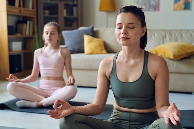 Calma mãe de meia-idade meditando de olhos fechados junto com a filha em casa
