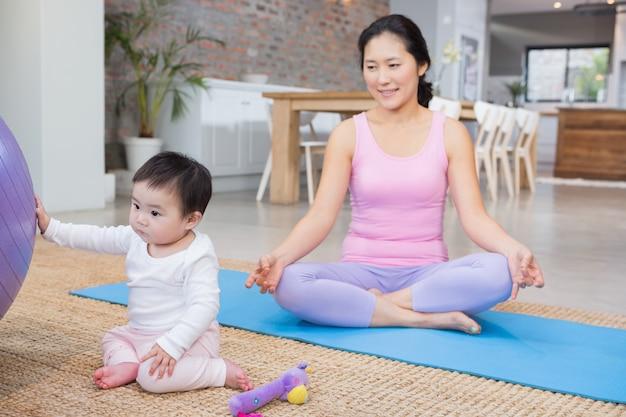 Calma mãe sentada na esteira em casa enquanto filha brincando com bola de fitness