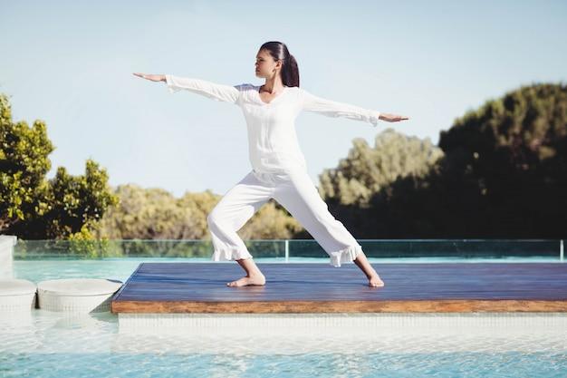 Calma morena fazendo ioga à beira da piscina