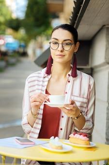 Calma. mulher atraente e calma sentada à mesa cheia de sobremesas deliciosas e segurando uma xícara de café