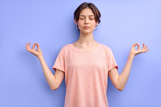 Calma mulher caucasiana, meditando com os olhos fechados, isolado sobre o fundo roxo, envolvida em ioga ke ...