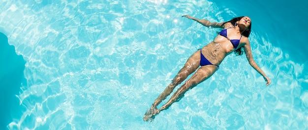 Calma mulher flutuando na piscina em um dia ensolarado