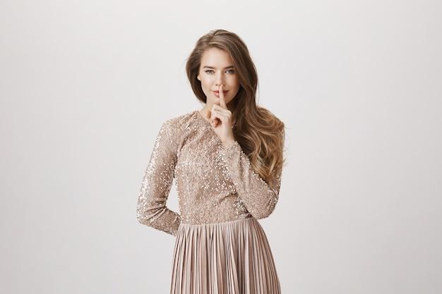 Calma mulher sensual, pressione o dedo indicador nos lábios, use vestido de noite