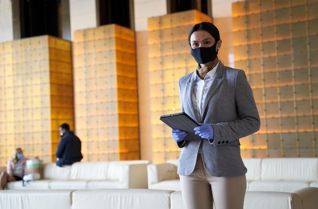 Calma senhora atraente em uma máscara e luvas de borracha em pé com um tablet nas mãos. pessoas sentadas no sofá ao fundo