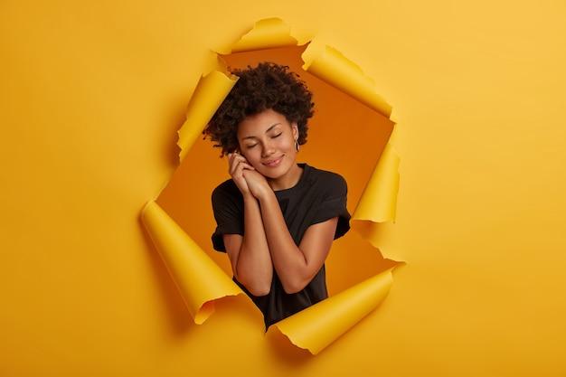 Calma sonhadora, cacheada, morena, modelo mantém os olhos fechados, inclina a cabeça sobre as mãos juntas, tem sonhos agradáveis, sorriso encantador, veste camiseta preta, fica em um buraco rasgado, fundo amarelo