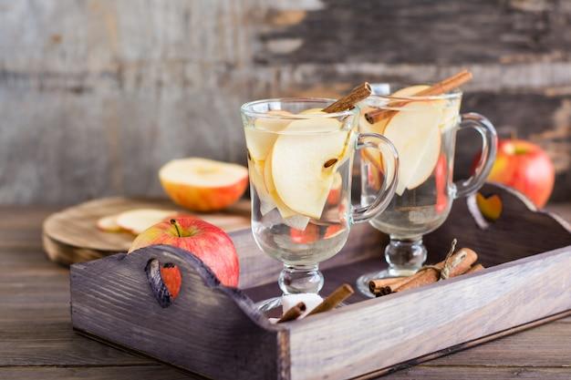 Calmante chá quente feito de maçãs e canela em copos em uma mesa de madeira. conceito de desintoxicação, antidepressivo. estilo rústico