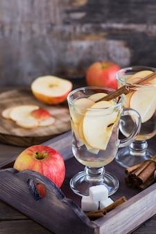 Calmante chá quente feito de maçãs e canela em copos em uma mesa de madeira. conceito de desintoxicação, antidepressivo.
