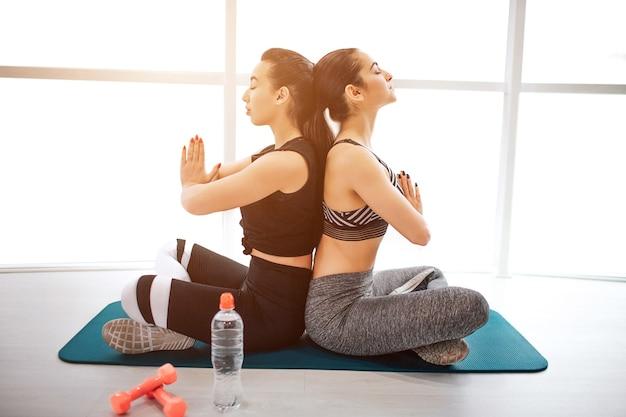 Calmas e concentradas jovens sportgirls sentam-se com as pernas cruzadas e meditam
