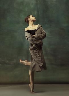 Caloroso. graciosa bailarina clássica dançando, posando isolada no fundo escuro do estúdio. casaco impermeável elegante. conceito de graça, movimento, ação e movimento. parece leve, flexível. na moda, estilo.