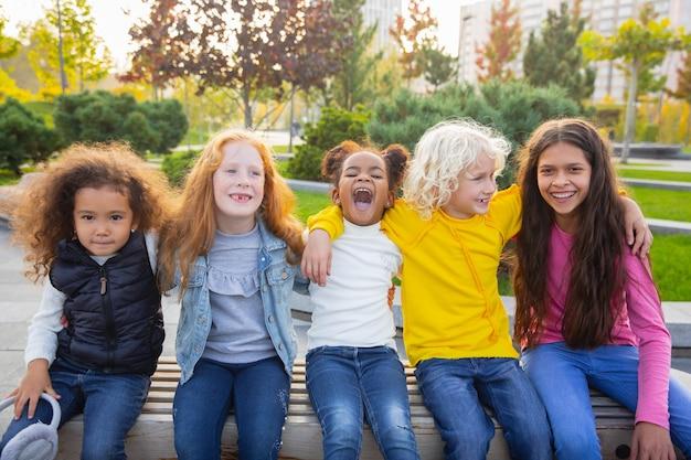 Caloroso. grupo inter-racial de crianças, meninas e meninos brincando juntos no parque num dia de verão.