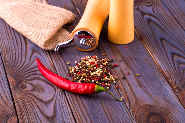 Calos de pimenta preta, pimenta vermelha quente e pimenta preta em pó na mesa de madeira