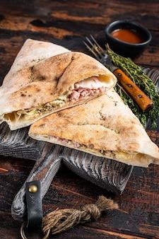 Calzone caseiro fechado pizza com presunto e queijo na placa de madeira. fundo de madeira escuro. vista do topo.