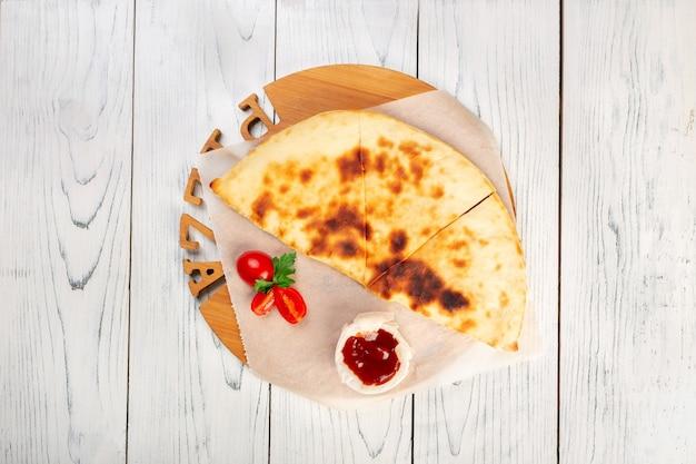 Calzone de pizza fechado com molho sobre um fundo claro de madeira, vista superior com espaço de cópia.