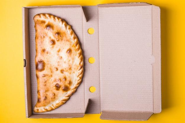 Calzone de pizza fechado em uma caixa de embalagem em um fundo amarelo.