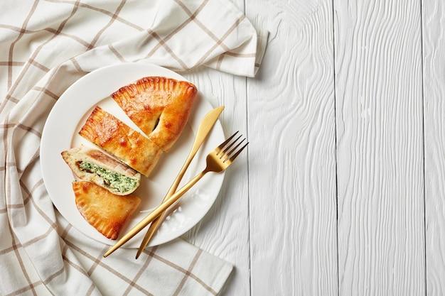 Calzones com recheio de espinafre e queijo servido em um prato branco com garfo e faca de ouro sobre uma mesa de madeira, flatlay, copie espaço