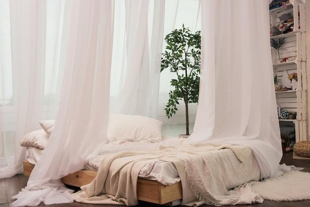Cama aconchegante perto da janela com belas cortinas no quarto.