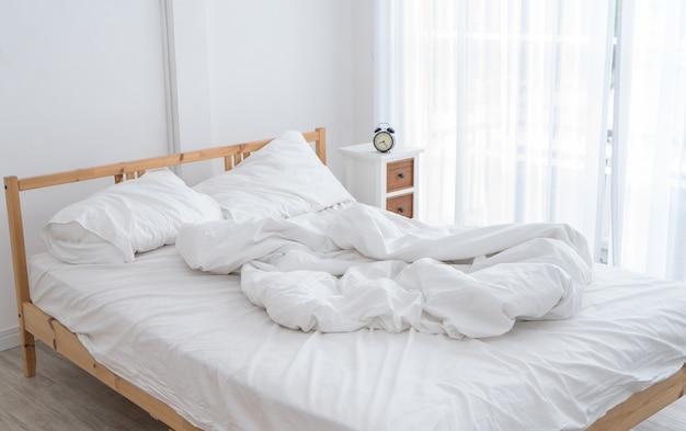 Cama bagunçada branca em uma sala branca na manhã sem pessoas