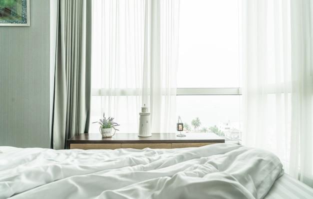 Cama bagunçada com cortina e janela