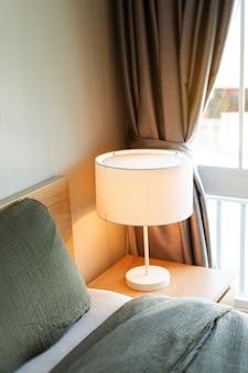 Cama com cobertor cinza e travesseiro com lâmpada elétrica branca na mesinha de cabeceira do quarto