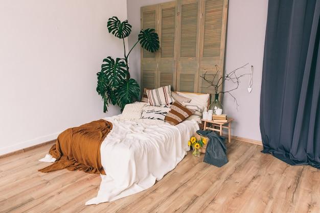 Cama com cobertores e travesseiros em um quarto. interior do quarto. loft