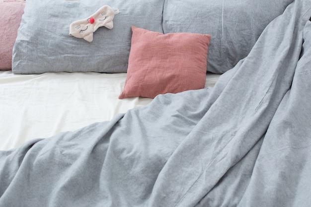 Cama com lençóis cinza e máscara de dormir