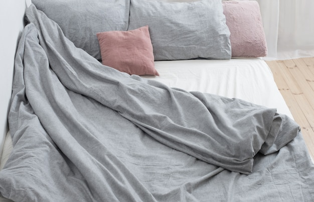 Cama com lençóis cinza em interior branco