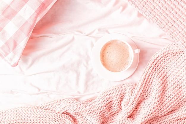Cama com manta de malha rosa e café