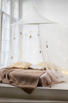 Cama com roupa de cama estampada e cortinas brancas