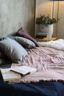 Cama com travesseiros e livro aberto
