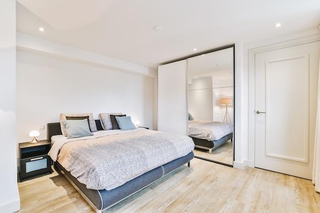 Cama confortável com cobertor e travesseiros localizados perto de lâmpadas e cadeira em quarto espaçoso em apartamento moderno