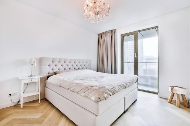 Cama confortável com cobertor macio e mesa de cabeceira de madeira sob um lustre de luxo no quarto