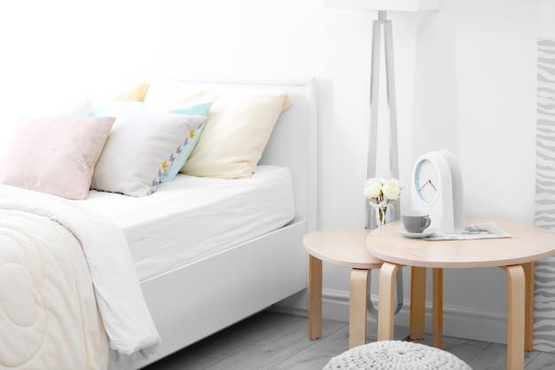 Cama confortável com colcha bege macia e travesseiros em quarto moderno e claro