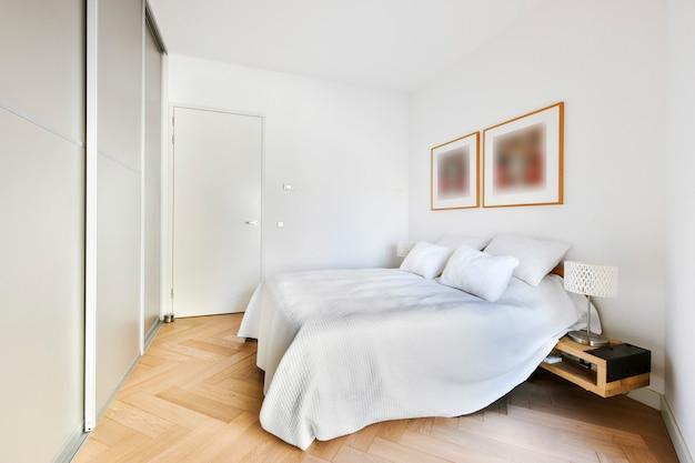 Cama confortável com linho branco e almofadas em quarto claro com moldura na parede e guarda-roupa embutido
