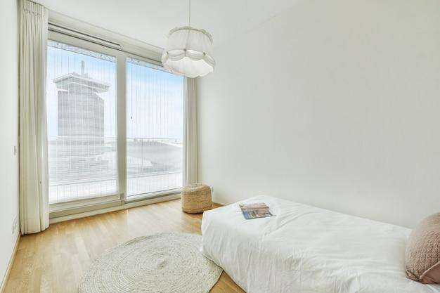 Cama confortável com travesseiro e revista localizada em quarto claro com parede branca e janela grande em apartamento moderno