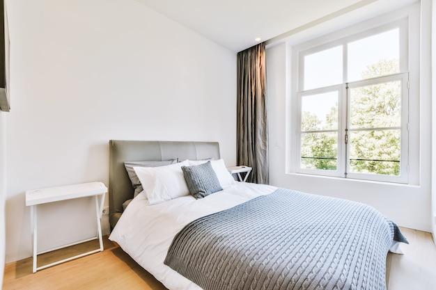 Cama confortável e carpete macio em quarto espaçoso com interior em estilo minimalista