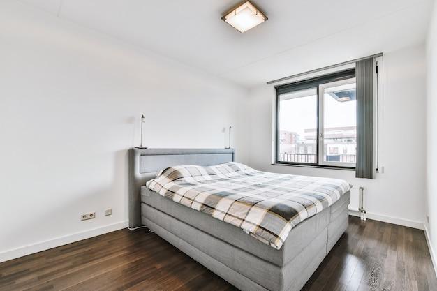 Cama confortável localizada perto da janela com cortina no quarto claro de apartamento contemporâneo