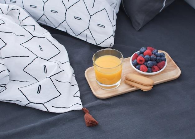 Cama de café da manhã bandeja de madeira interior da manhã cedo lençol e fronha geométrica bagas suco de laranja biscoitos