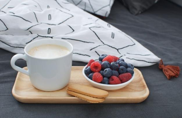 Cama de café da manhã bandeja de madeira interior da manhã espaço para cópias lençol geométrico e fronha bagas biscoitos cappuccino