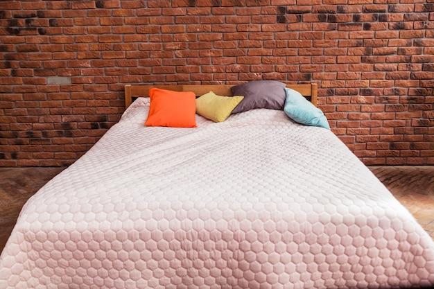 Cama de casal moderna com uma manta e travesseiros coloridos fica contra um fundo de parede de tijolos. foto horizontal