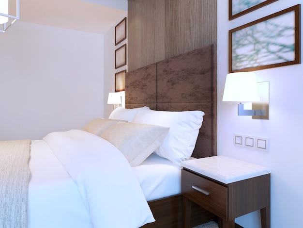 Cama de casal vestida em quarto moderno com tema branco e móveis marrons.