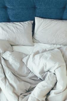 Cama de empregada com almofadas brancas limpas e lençóis na sala de beleza. fechar-se.