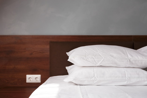 Cama de empregada com almofadas brancas limpas e lençóis na sala de beleza.