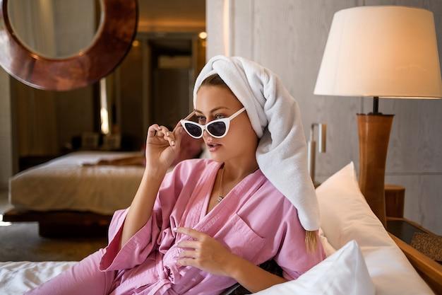 Cama de jovem mulher sentada no interior do quarto moderno com seu laptop e trabalho. quarto moderno. relaxamento após dias de trabalho.