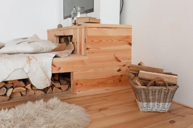 Cama de madeira e lenha sob ela, cesta cheia de lareira