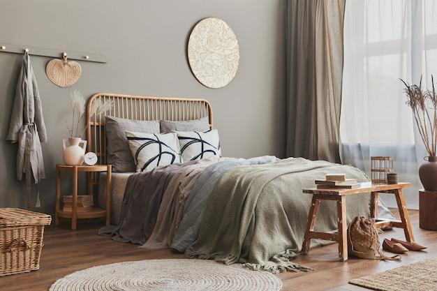 Cama de madeira no interior de um quarto elegante e neutro com móveis de design, decoração, carpete, banco, flores secas em vasos, lençóis, cobertor, travesseiros e acessórios pessoais elegantes na decoração da casa.