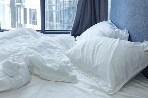 Cama de manhã amassada com roupa de cama branca