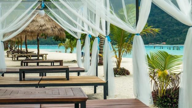 Cama de praia na areia branca entre palmeiras em pleno sol