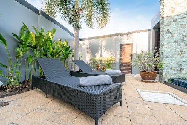 Cama de sol com guarda-chuva e plantas verdes na casa ou construção de casas